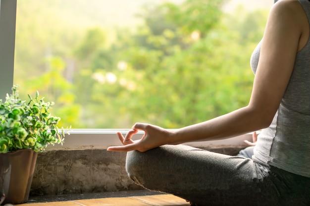 Frau sitzt neben dem fenster und macht yoga