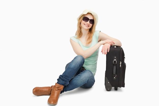 Frau sitzt neben einem koffer