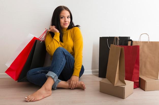 Frau sitzt neben einkaufstüten