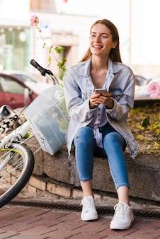 Frau sitzt neben ihrem fahrrad