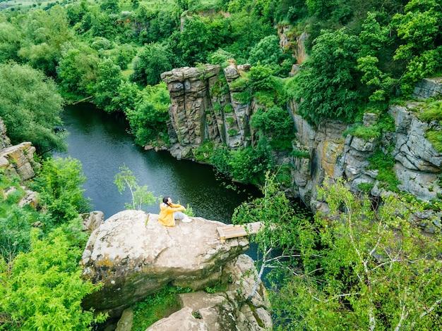 Frau sitzt oben und genießt den blick auf den canyon-flusswald