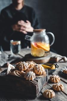 Frau sitzt über einer tasse heißen tees mit scheiben der frischen grapefruit auf holztafel