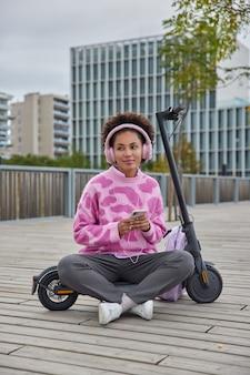 Frau sitzt überkreuzte beine hört lieblingsmusik in kopfhörern trägt lässige pulloverhosen und turnschuhe reitet elektro-tretroller-posen in urbaner umgebung
