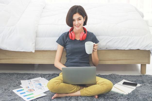 Frau sitzt und benutzt computer im schlafzimmer