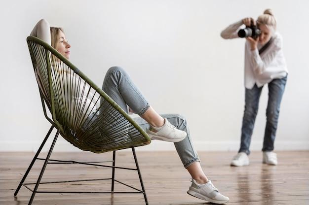 Frau sitzt und fotograf macht fotos