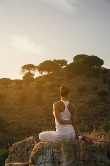 Frau sitzt und streckt in der natur