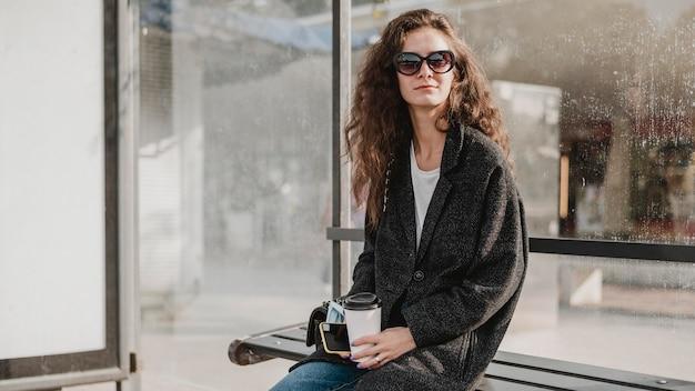 Frau sitzt und wartet in der bushaltestelle