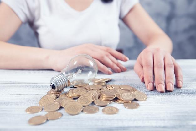 Frau sitzt vor einer glühbirne und münzen