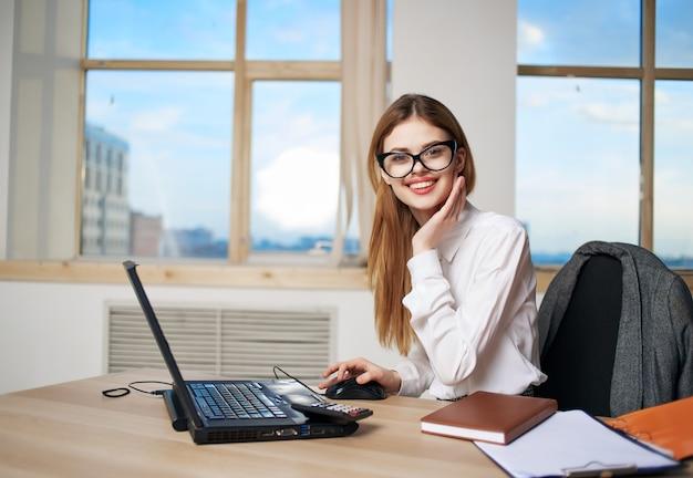 Frau sitzt vor laptop im büro sekretärin berufstätigen