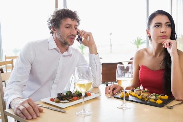 Frau sitzt, während mann mobiltelefon spricht