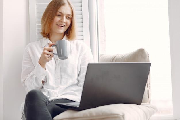 Frau sitzt zu hause und benutzt einen laptop