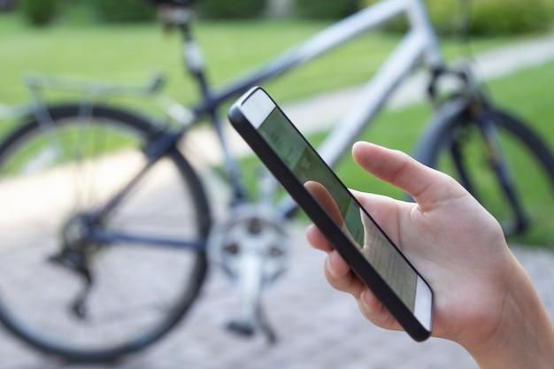 Frau smartphones in der hand auf unscharfem fahrradhintergrund. mobilfunknetz.