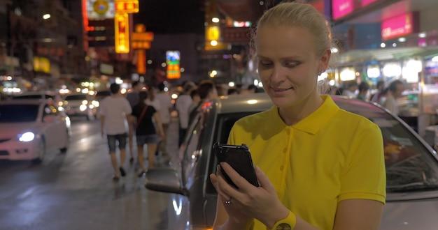 Frau sms auf zelle und blick auf nacht bangkok thailand
