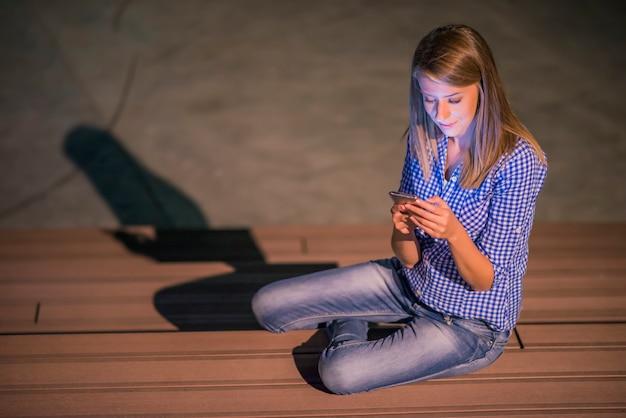 Frau sms. closeup junge glücklich lächelnd fröhlich schöne frau blick auf mobile handy lesen senden sms isoliert park cityscape im freien hintergrund. positives gesichtsausdruck menschliches gefühl