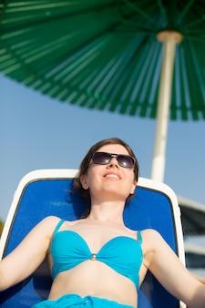 Frau sonnenbaden unter grünen sonnenschirm