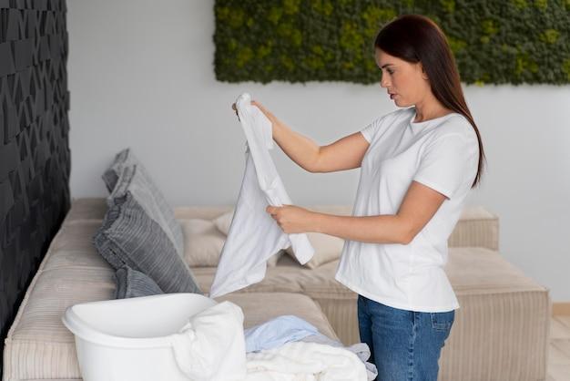 Frau sortiert frisch gereinigte kleidung aus