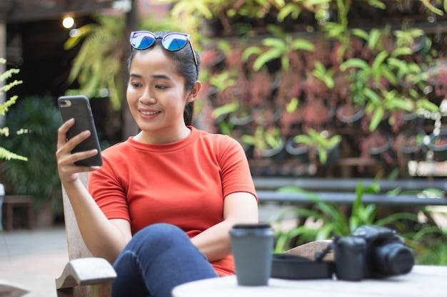 Frau spielen internet auf handys und haben eine kamera, eine kaffeetasse ist auf einem hölzernen tisch