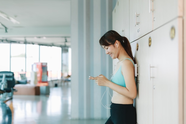 Frau spielen telefon nach dem trainieren in der turnhalle.