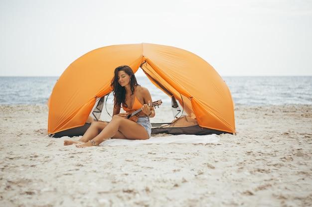 Frau spielt die ukelele mit einem orangefarbenen zelt am strand