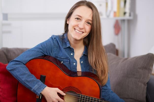 Frau spielt gitarre zu hause