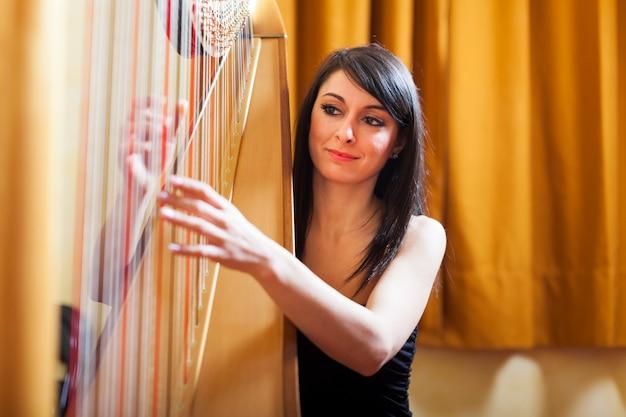 Frau spielt harfe