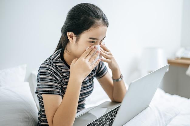 Frau spielt laptop und hält ein taschentuch, um eine nase abzuwischen.
