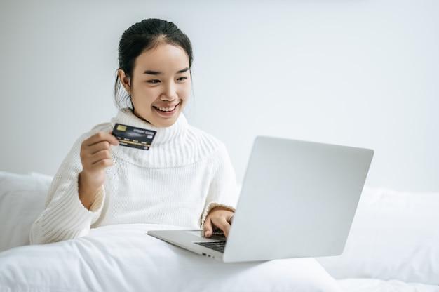 Frau spielt laptop und hält eine kreditkarte.