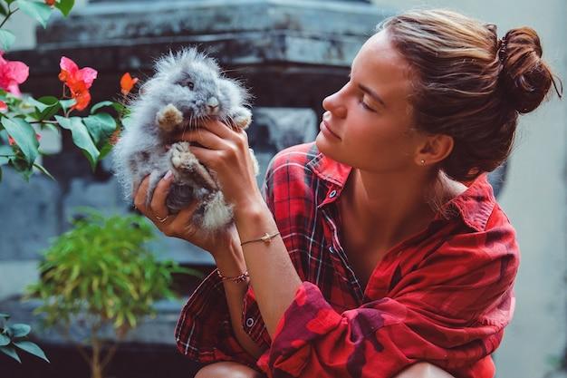 Frau spielt mit einem kleinen kaninchen.
