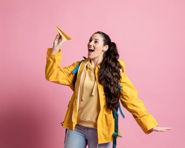 Frau spielt mit einem papier gemacht flugzeug