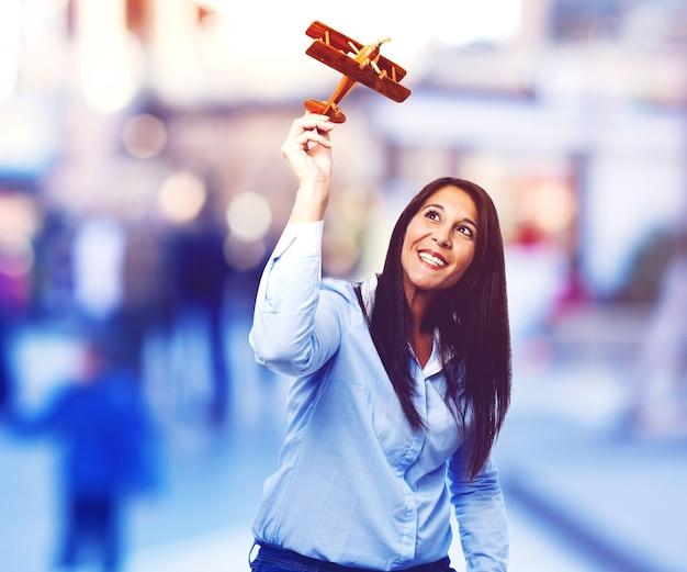 Frau spielt mit einem spielzeug-flugzeug