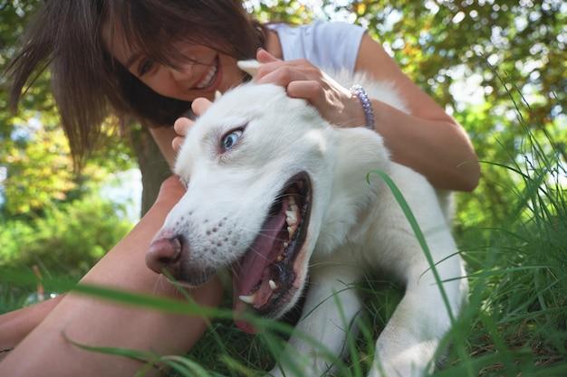 Frau spielt mit ihrem glücklichen hund, der zunge aus vergnügen hält