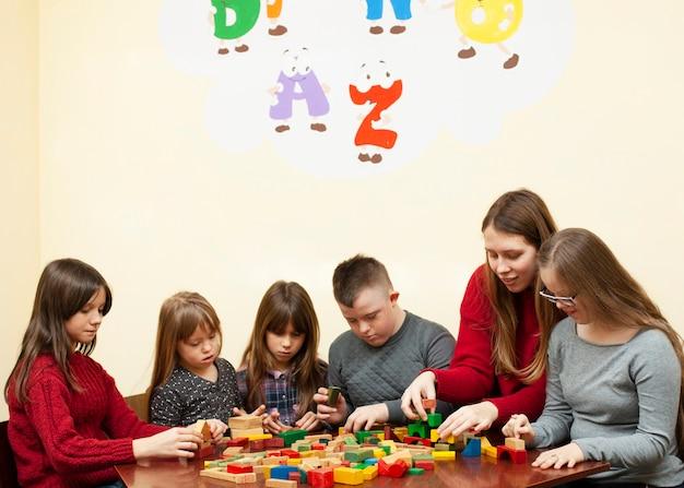 Frau spielt mit kindern mit down-syndrom und blockaden