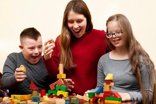 Frau spielt mit kindern mit down-syndrom