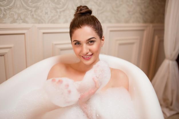 Frau spielt mit schaum in der badewanne.