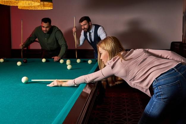 Frau spielt snooker, sie zielt darauf ab, den snooker-ball zu schießen und hände auf dem snooker-tisch zu halten. billard