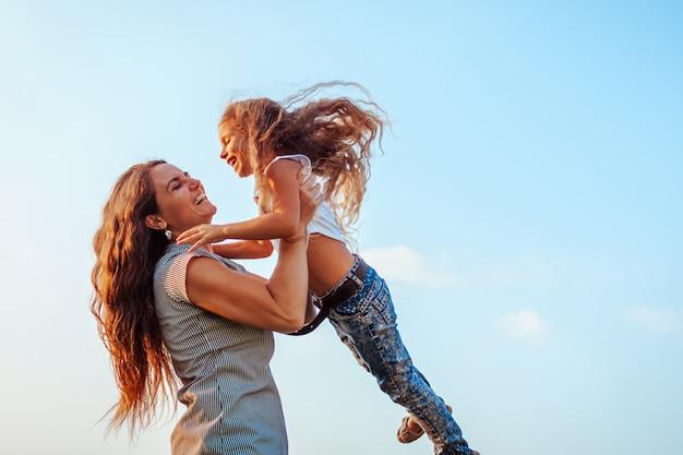 Frau spielt und hat spaß mit kind durch sommerfluss