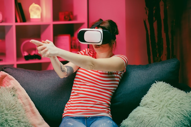 Frau spielt und lächelt im vr-headset. virtual-reality-helm auf farbbeleuchtung