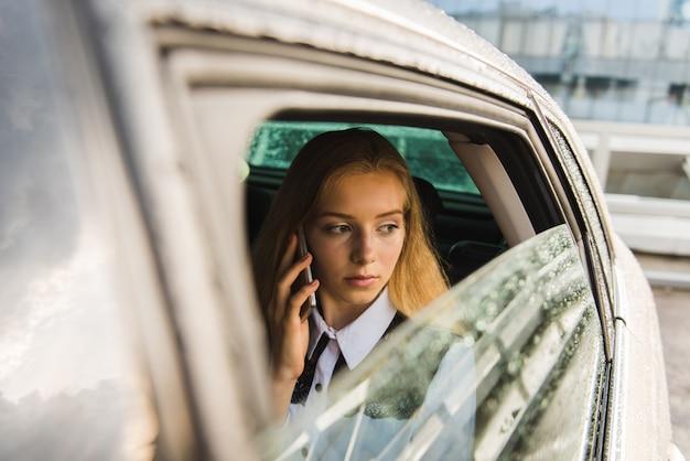 Frau spricht am regnerischen tag im auto per telefon