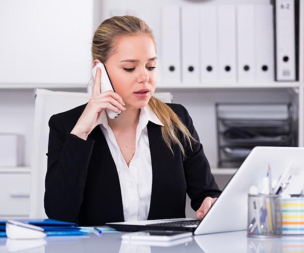 Frau spricht am telefon im büro