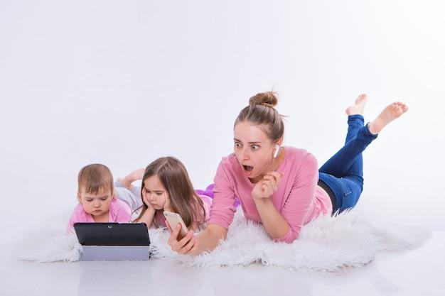 Frau spricht am telefon über headset, kinder sehen cartoon auf tablet