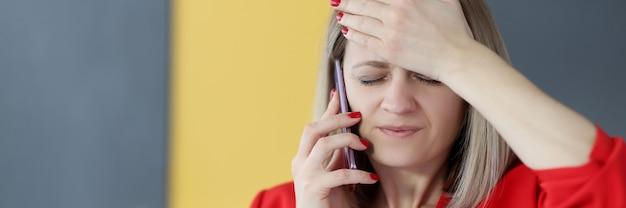 Frau spricht am telefon und hält ihre stirn mit ihrer handgedächtnisstörung