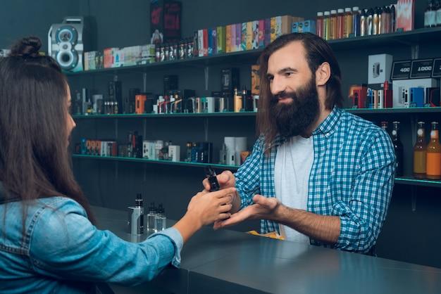 Frau spricht mit dem verkäufer - einem großen mann mit langen haaren.