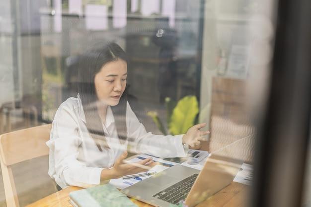 Frau spricht mit leuten in einem videoanruf auf dem laptop. geschäftsfrauen verwenden videokonferenzen, um in organisationen auf der ganzen welt zu kommunizieren. telefonkonferenzen werden in unternehmen und bildungseinrichtungen eingesetzt.