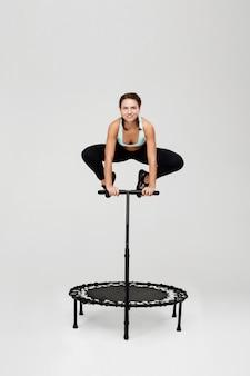 Frau springt auf rebounder mit biegeknien, die griff halten