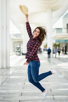Frau springt mit einem strohhut