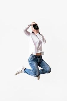 Frau springt und benutzt ihr kamerafoto