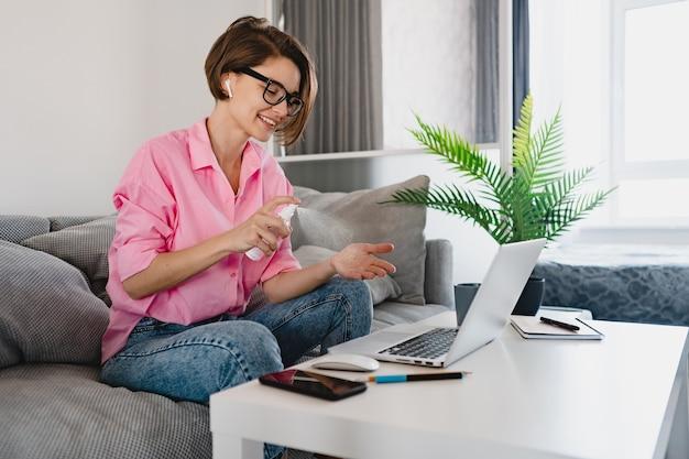 Frau sprüht desinfektionsmittel antiseptisch auf die hände am arbeitsplatz zu hause, die online am laptop arbeitet
