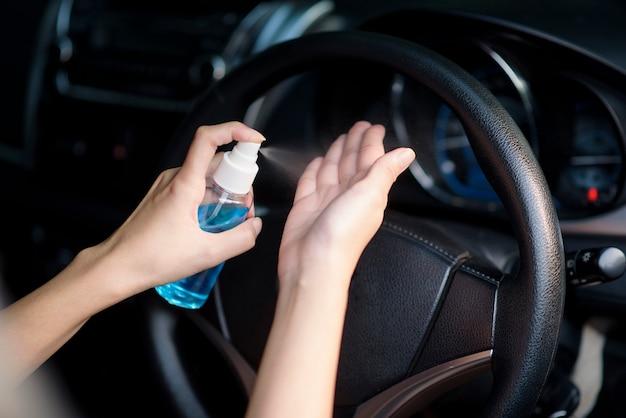 Frau sprüht händedesinfektionsmittel auf ihre hände im auto