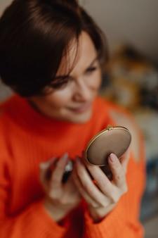 Frau sprüht parfüm, bevor sie sich auf den weg macht