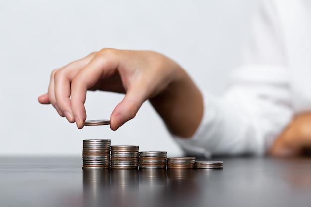 Frau stapelt münzen in stapeln auf einem schwarzen tisch. das konzept des geldsparens, der finanz- und investitionspolitik.